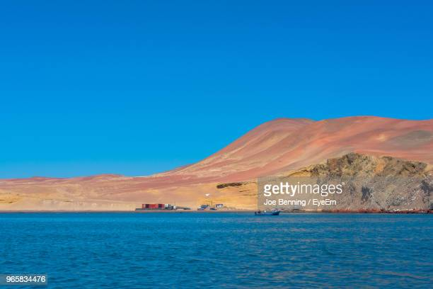 scenic view of sea against clear blue sky - pisco peru stock photos and pictures