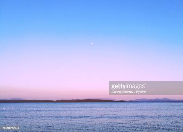 scenic view of sea against clear sky at night - pink moon stock pictures, royalty-free photos & images