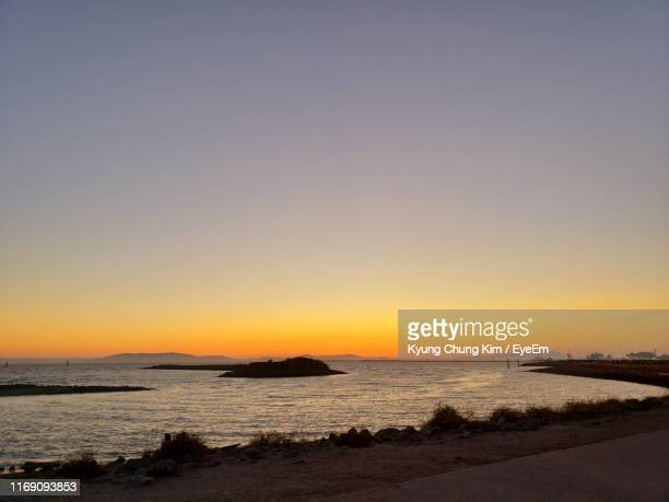 scenic view of sea against clear sky during sunset - san leandro stock photos and pictures