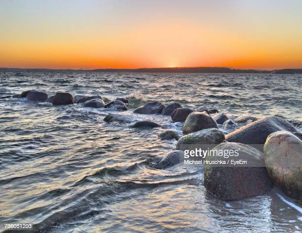 scenic view of sea against clear sky during sunset - michael hruschka stock-fotos und bilder