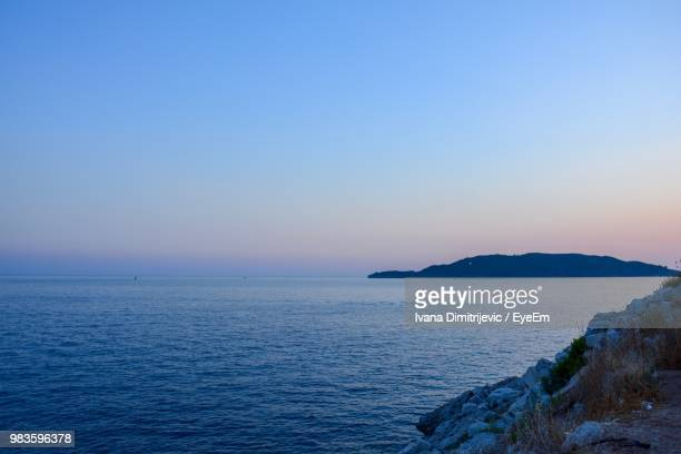 scenic view of sea against clear sky during sunset - rocky coastline stock pictures, royalty-free photos & images