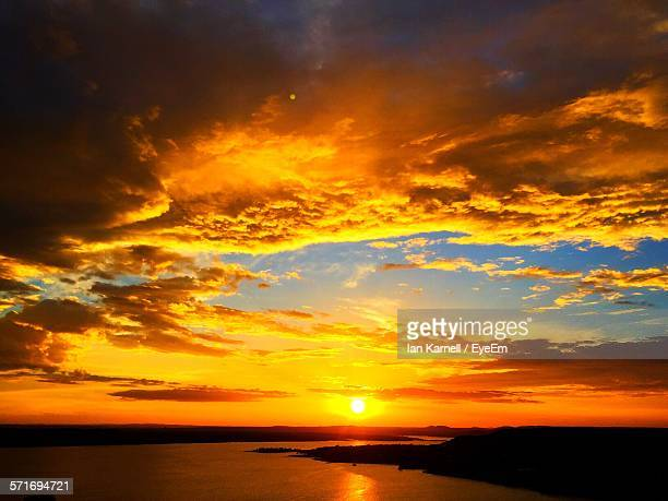 Scenic view of sea against cloudy orange sky during sunset