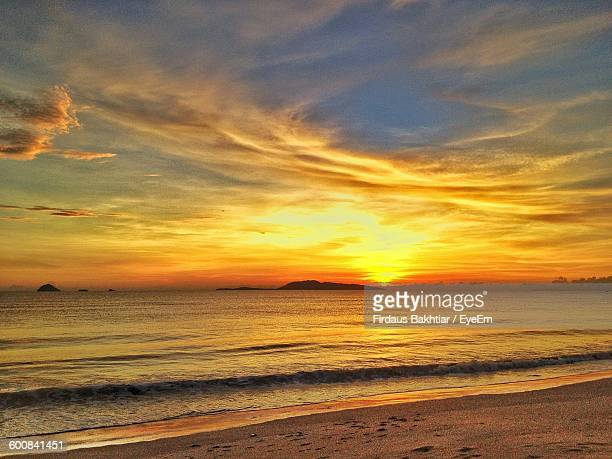 Scenic View Of Sea Against Cloudy Sky At Sunrise
