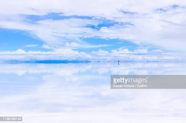 scenic view of sea against cloudy sky during sunny day - ウユニ塩湖 ストックフォトと画像