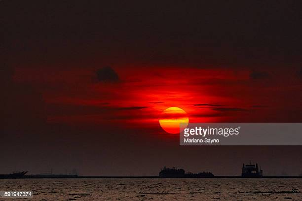 scenic view of sea against cloudy sky during sunset - manila bay stock photos and pictures