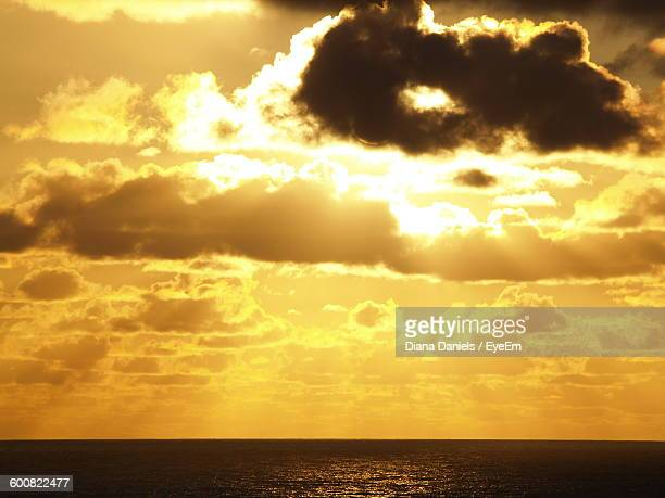 scenic view of sea against cloudy sky during sunset - diana daniels stock-fotos und bilder