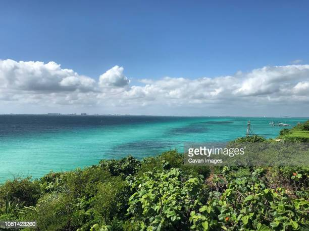 scenic view of sea against cloudy sky - isla mujeres stock photos and pictures