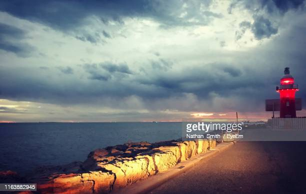scenic view of sea against cloudy sky - 防波堤 ストックフォトと画像