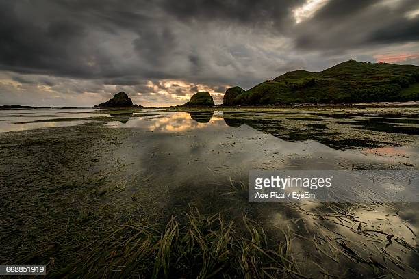 scenic view of sea against cloudy sky - ade rizal stock photos and pictures