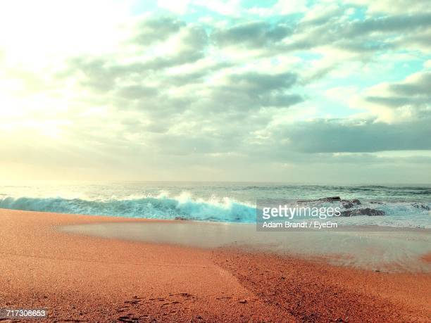 scenic view of sea against cloudy sky - durban beach stock photos and pictures
