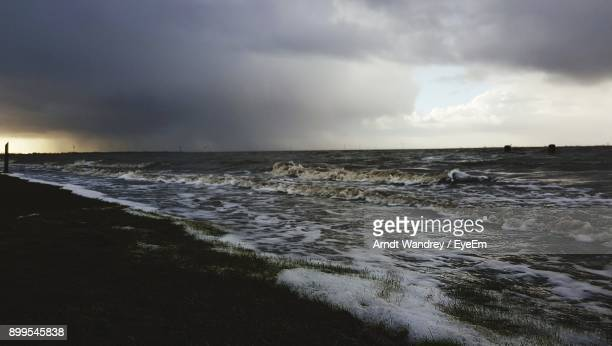scenic view of sea against cloudy sky - husum stock-fotos und bilder