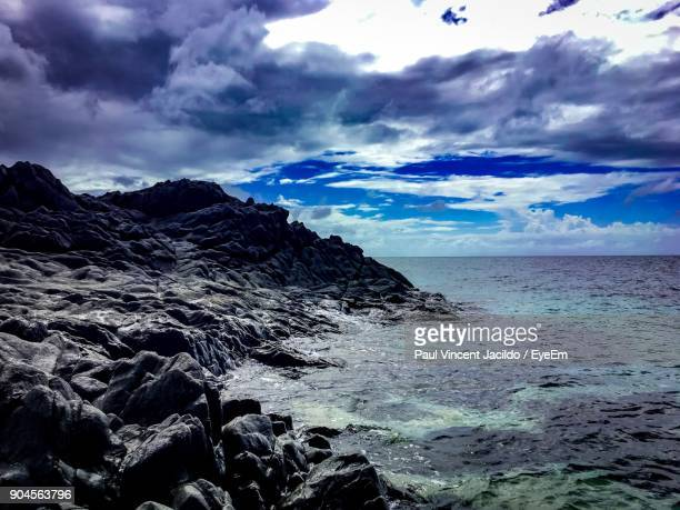 scenic view of sea against cloudy sky - davao city stock photos and pictures