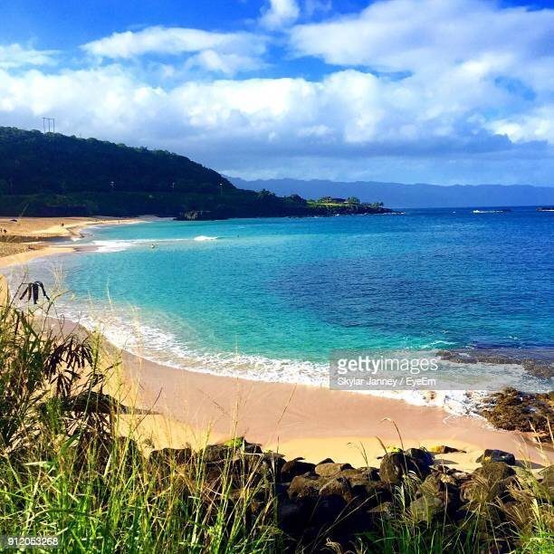 scenic view of sea against cloudy sky - waimea bay stock photos and pictures