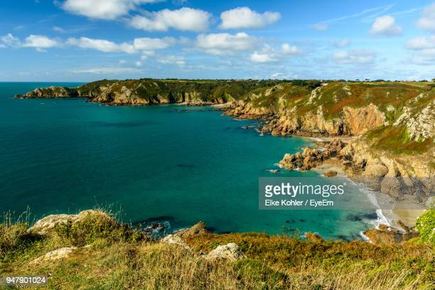 scenic view of sea against cloudy sky - isola di guernsey foto e immagini stock