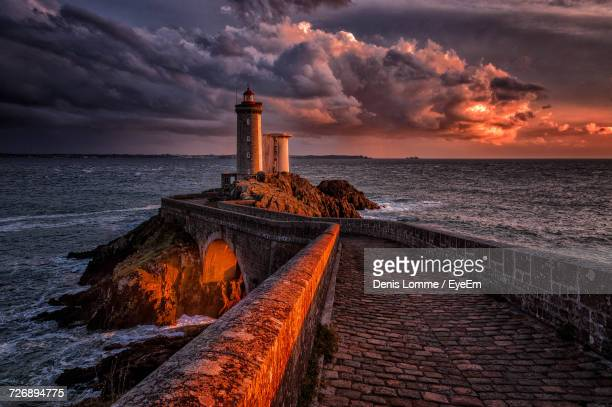 Scenic View Of Sea Against Dramatic Sky At Sunset