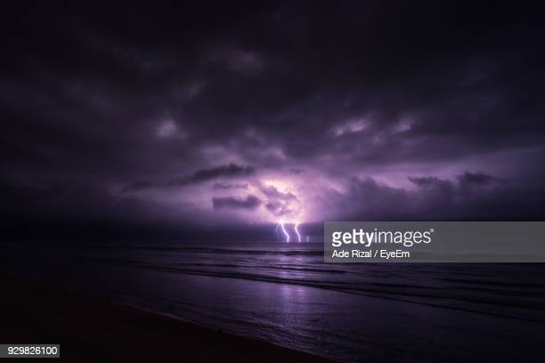 scenic view of sea against dramatic sky at sunset - ade rizal stock photos and pictures