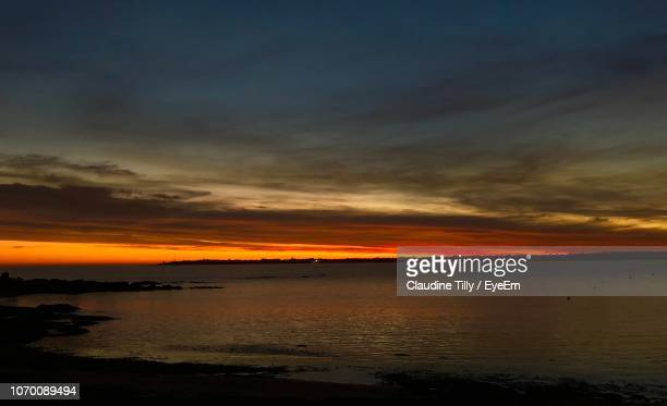 scenic view of sea against dramatic sky during sunset - concarneau stock-fotos und bilder