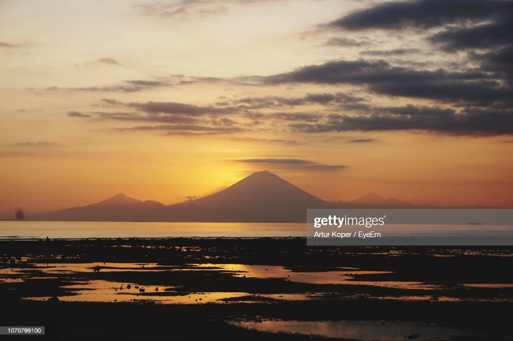 Scenic View Of Sea Against Dramatic Sky During Sunset : Stock Photo