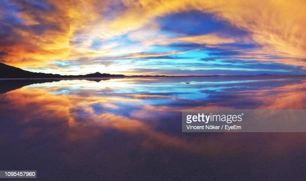 scenic view of sea against dramatic sky during sunset - ウユニ ストックフォトと画像