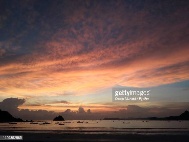 scenic view of sea against dramatic sky during sunset - oppie muharti stock pictures, royalty-free photos & images