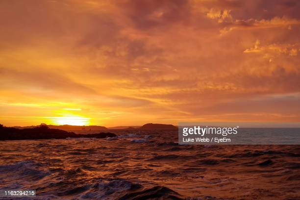 scenic view of sea against dramatic sky during sunset - red stock pictures, royalty-free photos & images