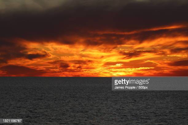 scenic view of sea against dramatic sky during sunset - james popple stock pictures, royalty-free photos & images