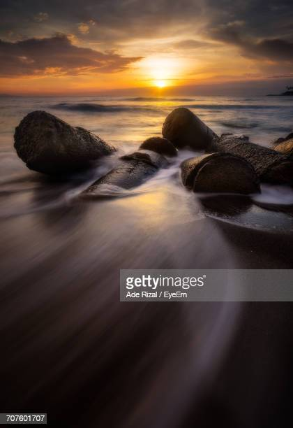 scenic view of sea against dramatic sky during sunset - ade rizal stock photos and pictures