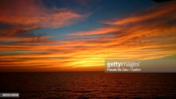 scenic view of sea against dramatic sky during sunset - freude stockfoto's en -beelden