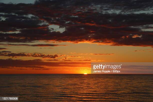 scenic view of sea against dramatic sky during sunset,glenelg south,south australia,australia - james popple foto e immagini stock
