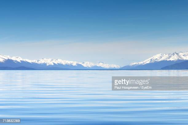 scenic view of sea against mountain range - horizon over land stock photos and pictures