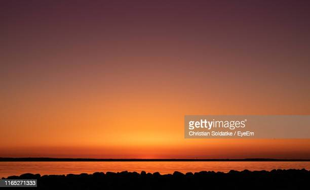 scenic view of sea against orange sky during sunset - christian soldatke stock pictures, royalty-free photos & images