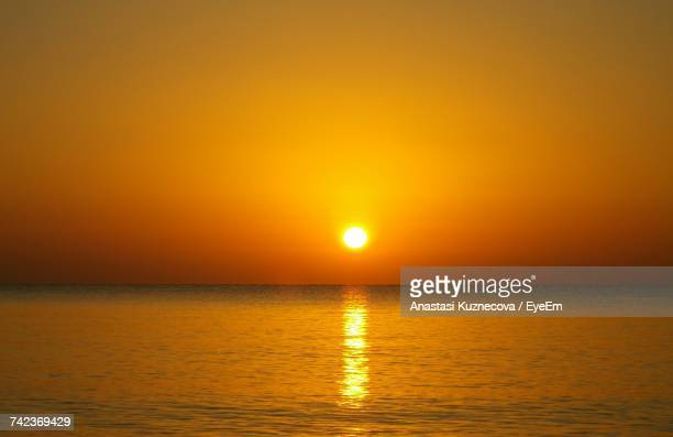scenic view of sea against orange sky during sunset - anastasi foto e immagini stock