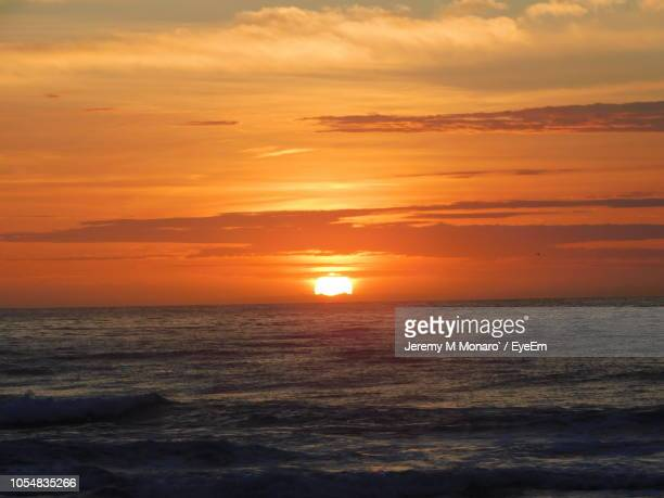 scenic view of sea against orange sky - jeremy monaro stock pictures, royalty-free photos & images