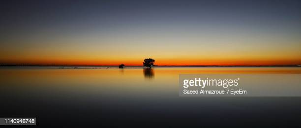 scenic view of sea against orange sky - abu dhabi stock pictures, royalty-free photos & images