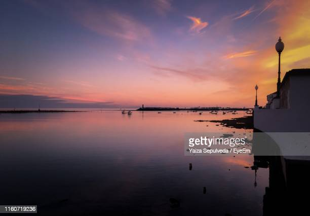 scenic view of sea against orange sky - arrecife stock photos and pictures
