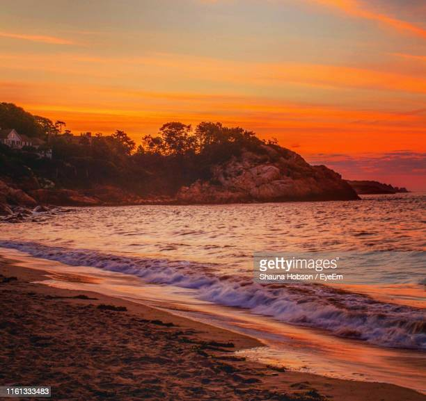 scenic view of sea against orange sky - manchester by the sea massachusetts stock pictures, royalty-free photos & images