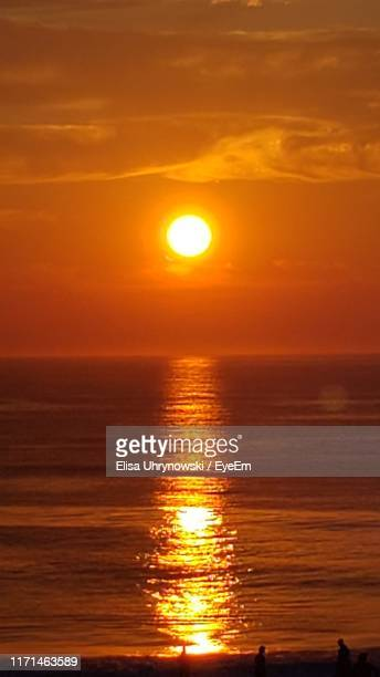 scenic view of sea against orange sky - kitty hawk beach stock pictures, royalty-free photos & images