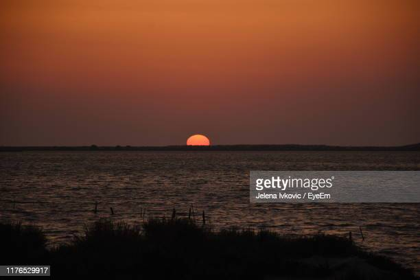 scenic view of sea against orange sky - jelena ivkovic stock pictures, royalty-free photos & images
