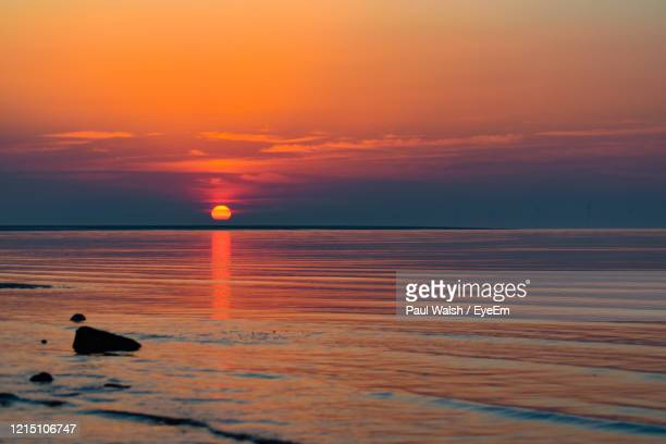 scenic view of sea against orange sky - night stock pictures, royalty-free photos & images