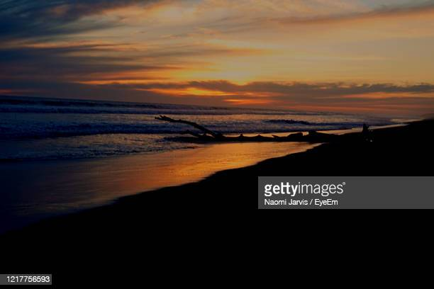 scenic view of sea against orange sky - naomi jarvis stock pictures, royalty-free photos & images