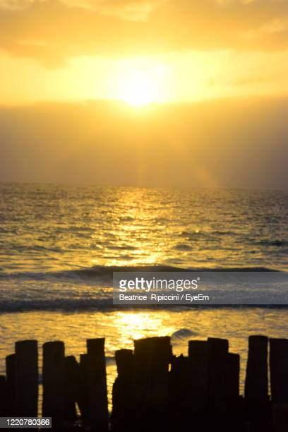 scenic view of sea against orange sky - beatrice stock pictures, royalty-free photos & images
