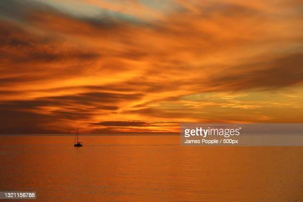 scenic view of sea against orange sky - james popple foto e immagini stock