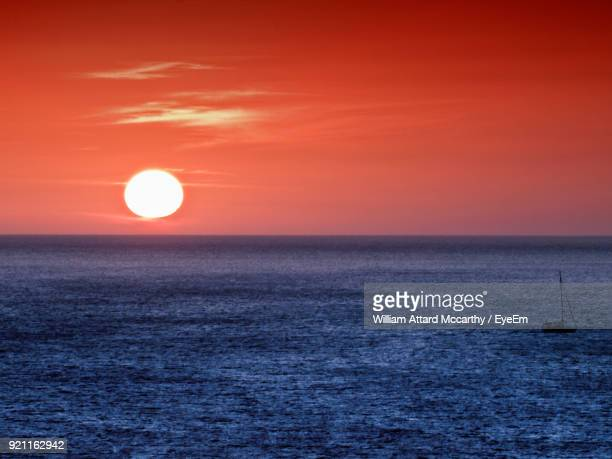 scenic view of sea against orange sky - william moon stock pictures, royalty-free photos & images