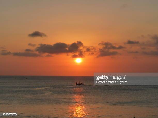 scenic view of sea against orange sky - marica octavian stock photos and pictures