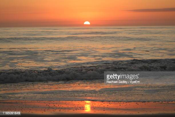 scenic view of sea against romantic sky at sunset - cocoa beach stock pictures, royalty-free photos & images
