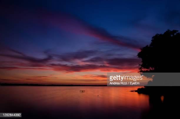 scenic view of sea against romantic sky at sunset - andrea rizzi stockfoto's en -beelden