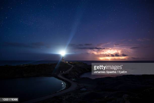 scenic view of sea against sky at night - lighthouse stock pictures, royalty-free photos & images