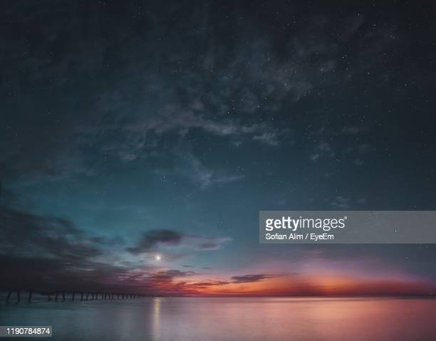 scenic view of sea against sky at night - dramatic sky stock pictures, royalty-free photos & images