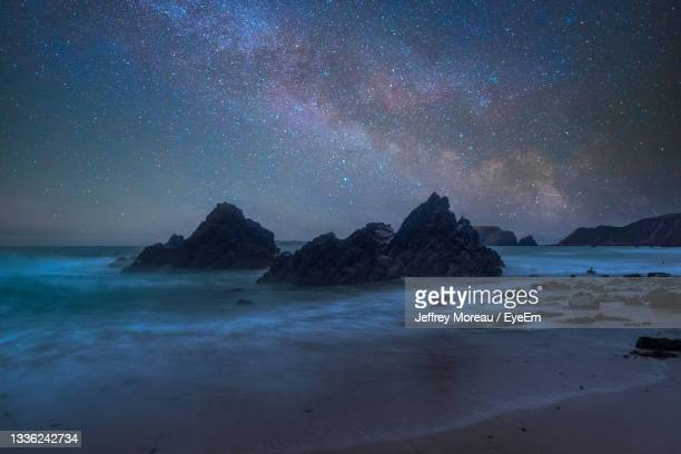 scenic view of sea against sky at night - space and astronomy stock pictures, royalty-free photos & images