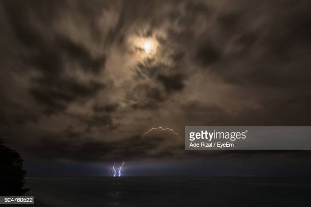 scenic view of sea against sky at night - ade rizal stock photos and pictures